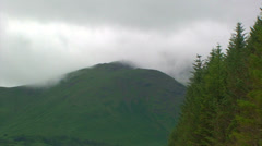 Fast clouds over a mountain top and spruce forest in Highlands Stock Footage