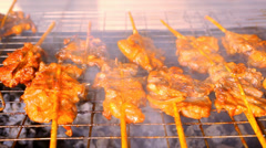 Close up frying pieces of meat in the grill on wooden sticks. Macro video Stock Footage