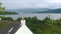 House roof in front of a large loch / kyle Stock Footage