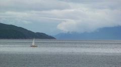 Sailing boat crossing cloudy fjord to the right Stock Footage