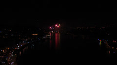 Firework over city at night with reflection in water Stock Footage