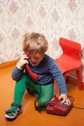 Young boy using red phone Stock Photos