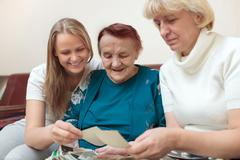 Mother, daughter and grandma looking at photos - stock photo