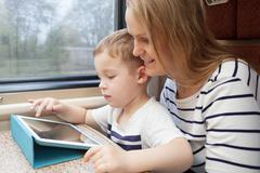 Mother and her young son on a train - stock photo