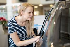 Woman admiring a car at an auto show - stock photo