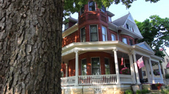 Dolly past a tree reveals the large Victorian Home - stock footage