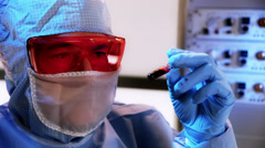 Closeup CDC or biohazard lab tech looking at a blood sample Stock Footage