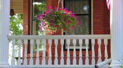 Porch of a large Victorian home with a basket of flowers waving in the wind Stock Footage