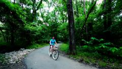 Classic beach cruiser bicycle riding through the woods Stock Footage