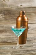 mixed drink and metal mixer on rustic wood - stock photo