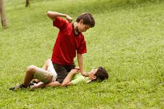 violent kid fighting and hitting scared boy in park - stock photo