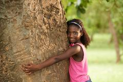 portrait of black ecologist girl hugging tree and smiling - stock photo