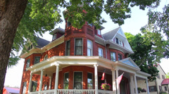 Large Victorian home in a small town.  Dolly reveal from a large tree - stock footage