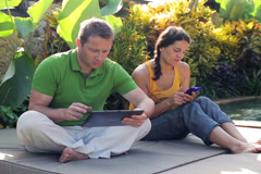 Happy couple talking and using tablet in garden Stock Footage