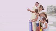 Three Caucasian Girls Parents Fall Beach Vacation Bodyboards - stock footage