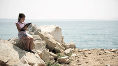 A child sits on a stone near the Adriatic Sea and draws a picture. Long shot. Stock Footage