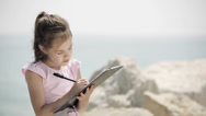 Stock Video Footage of A child sits on a stone near the Adriatic Sea and draws a picture. Close up.