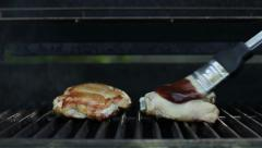 Basting chicken with BBQ sauce on a hot grill Stock Footage