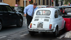 Big man with small fiat car Stock Footage