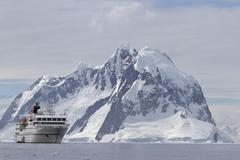 White tourist ship a summer day on a background of mountains of the antarctic Stock Photos