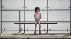 Child waiting for a bus at the bus stop looks around and misses. Model Elizabeth Stock Footage