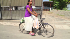 Local woman riding bicycle in Weligama, Sri Lanka. Stock Footage