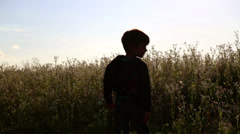 Boy running along the road in the field. Stock Footage