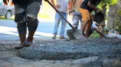 Stock Video Footage of Pouring cement on the road and workers alignment it. Video