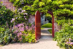 Medieval door, embedded in flowers, reveals secret walkway, building Stock Photos
