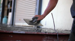 Closeup of mason's hand spreading concrete mix with trowel. Video Stock Footage