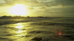 Tranquil Ocean Waves Under Gold Sunset Stock Footage