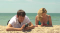 Young couple enjoys their smart phones lying on the beach near the sea Footage