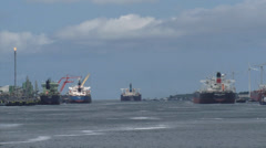 Oil tanker outbound to North Sea + zoom out Thialf maintenance platform moored Stock Footage