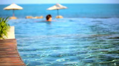 Woman swimming in pool and ocean at the background. Video shift motion Stock Footage