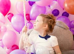 Stock Photo of Sympathetic little girl holding bunch of balloons