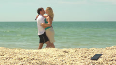 A young couple kissing at the sea leaving the phone in the sand - stock footage
