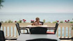 Child is drinking water in the restaurant which is located on the shore Stock Footage
