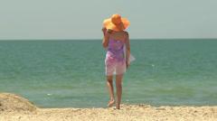 Young beautiful slim girl in orange hat walks along the seashore - stock footage