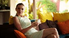 Kaunis liikenainen juomassa teetä, rentouttava sohvalla kotona HD Arkistovideo
