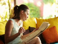 Businesswoman reading newspaper, eating snack on sofa at home NTSC - stock footage