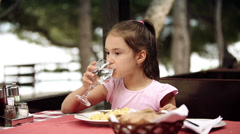 Child eats spaghetti pasta in the restaurant which is located on the shore Stock Footage
