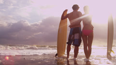 Young Ethnic Male Female Surfers Beach Ocean Shallows Sunset Stock Footage