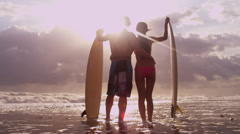 Male Female Surfers Sunset Beach Looking Ocean Stock Footage