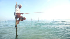Old fisherman on a fishing pole in the ocean in Galle, Sri Lanka. Stock Footage