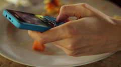 Close up of woman hand texting on smartphone and eating meal HD - stock footage
