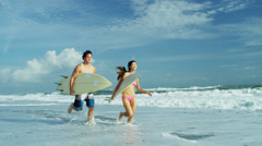 Male Female Ethnic Surfers Running Ocean Waves Stock Footage
