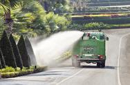 Stock Photo of water truck watering bush and shrub in park