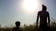Stock Video Footage of Young mother with her son in a field at sunset.