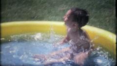 1091 - boy in backyard pool enjoyng the water - vintage film home movie Stock Footage