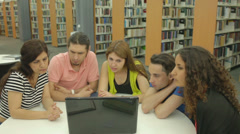 Group of five students watching training video in the library Stock Footage